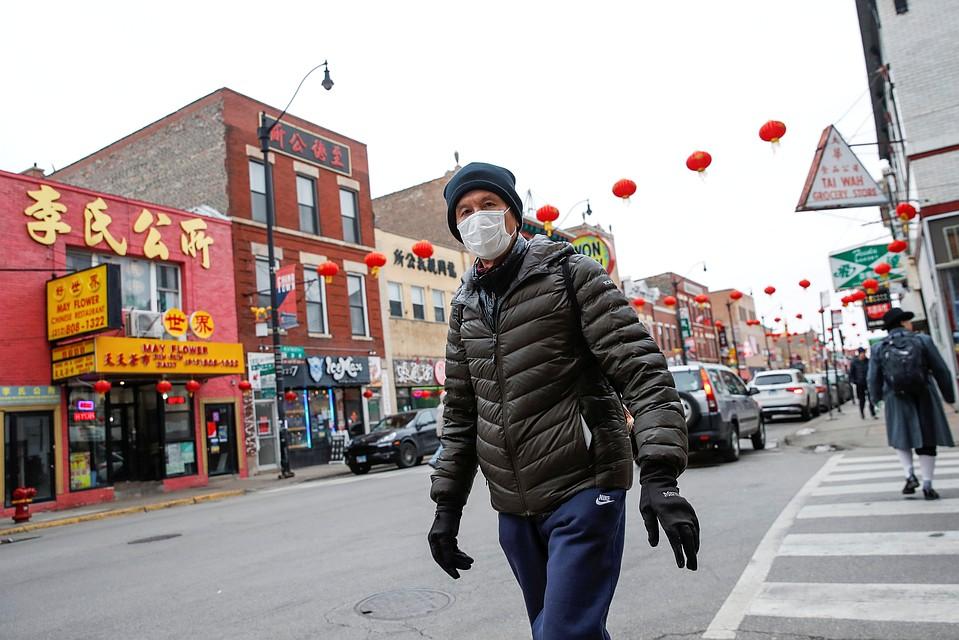 Прохожий в медицинской маске в китайском квартале Чикаго, США.