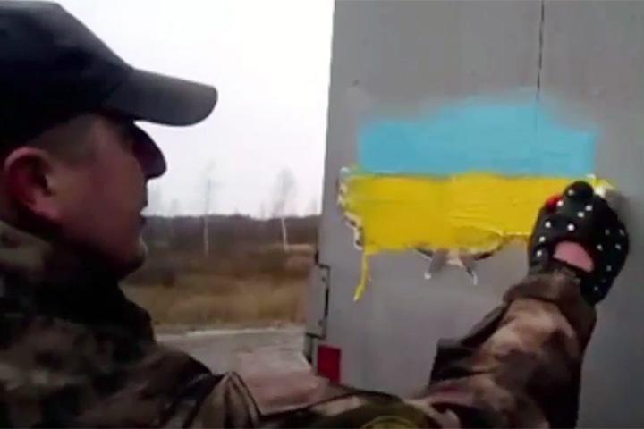 На кадрах щекастые здоровяки в разношерстных камуфляжных костюмах малюют на прицепе российской фуры украинский флаг