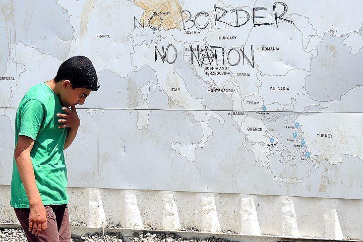 "Беженец на фоне надписи ""Нет границам! Нет нациям!"""