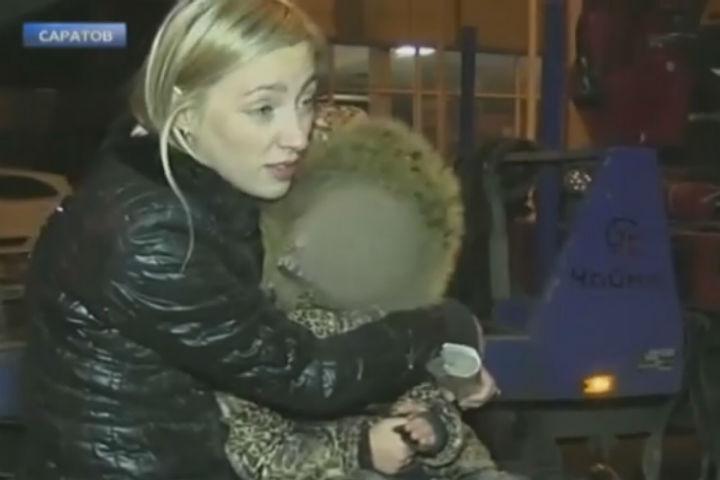 Под конец фееричного шоу мадам уселась с малышкой на капот, чтобы машину не забрали на штрафстоянку. Фото: скриншот видео НТВ.