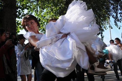 Женихи промчались наперегонки с невестами на руках по Красному проспекту. Фото: Андрей ГРЕБНЕВ