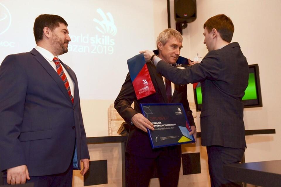 На церемонии назначения Сергею Крикалеву (в центре) вручили традиционные атрибуты WorldSkills - шарф с символикой чемпионата и именной сертификат посла. Фото: оргкомитет чемпионата WorldSkills Kazan 2019