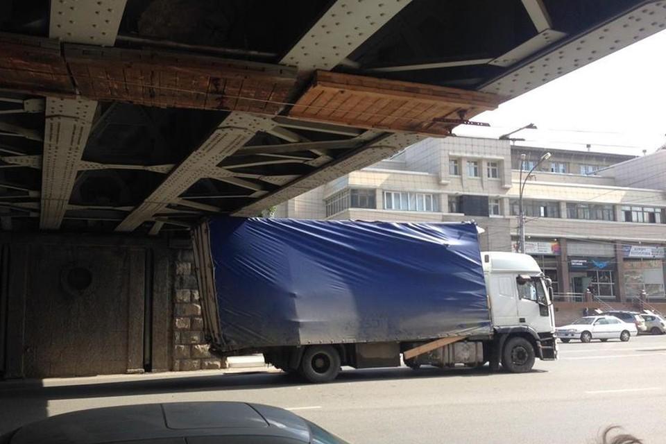 Грузовик с тентом попал в ловушку и застрял под мостом. Фото: Дмитрия Чечурова.