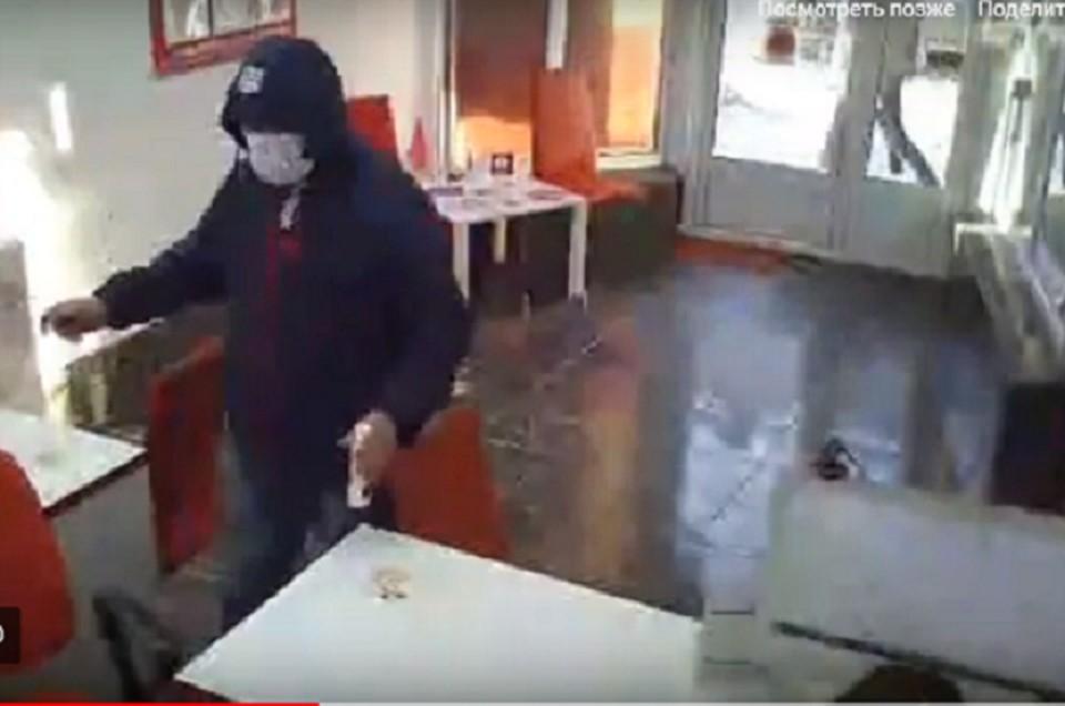 Мужчина ворвался в офис, стал требовать деньги и разливать жидкость для розжига. Фото: кадр видео.