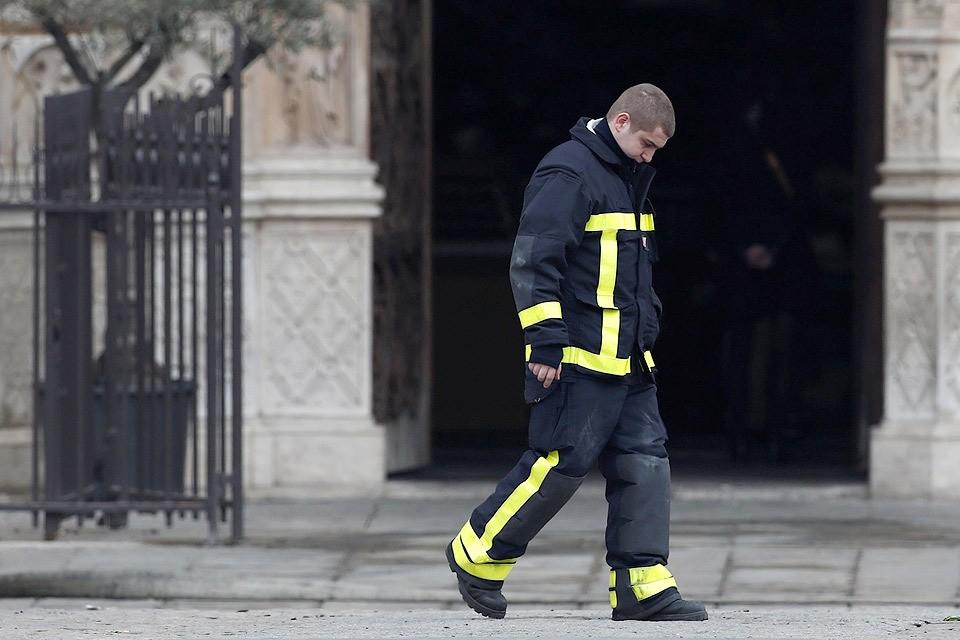 Парижский пожарный у стен главного собора города утром 16 апреля.
