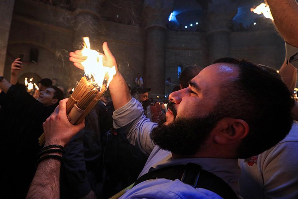 Свечи – особая история. Пучок из 33 свечей – важнейшая часть службы. Именно они должны подхватить огонь, который патриарх Иерусалимский выносит от гроба Господня. Фото: Владимир Смирнов/ТАСС