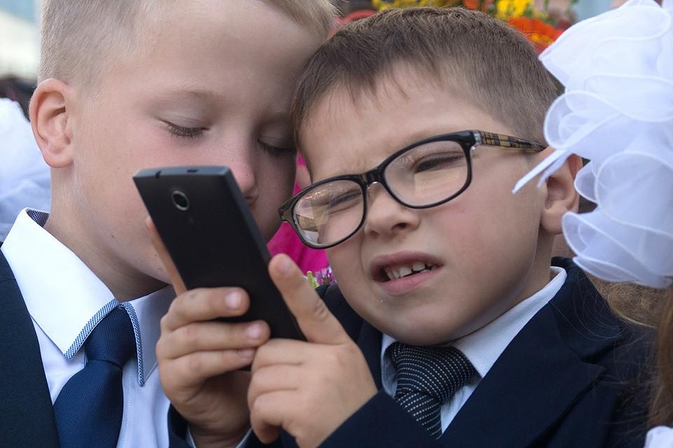 Школьник с мобильным телефоном на торжественной линейке 1 сентября.
