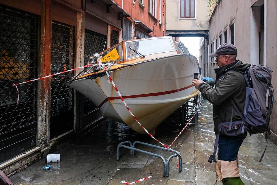 Поднявшаяся вода вынесла лодку на одну из узких улочек Венеции.