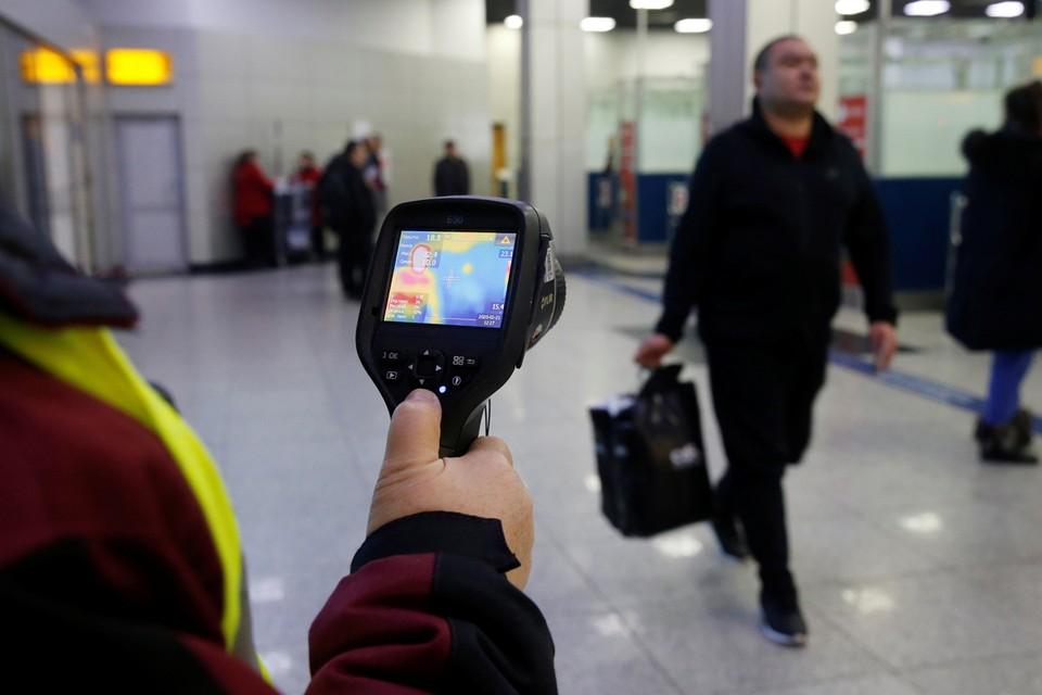 Проверка температурным сканером туристов, прилетающих из Китая, в Международном аэропорту Алматы в Казахстане.
