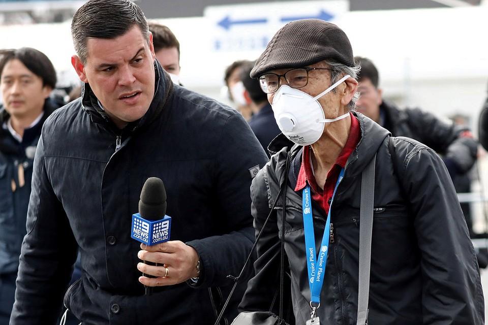 Репортер пытается взять интервью у пассажира круизного лайнера Diamond Princess, сошедшего на берег.