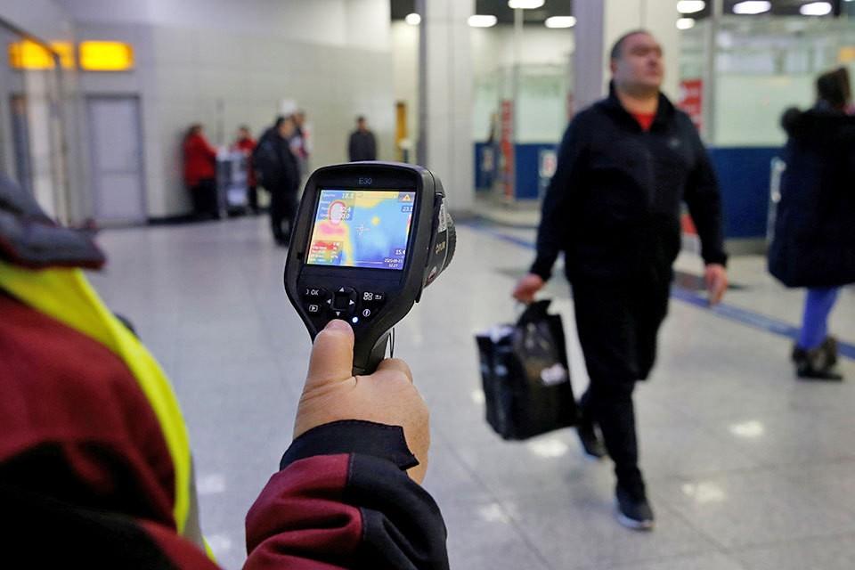 В международном аэропорту в Казахстане работник санитарно-эпидемиологический службы проверяет тепловизором пассажиров.