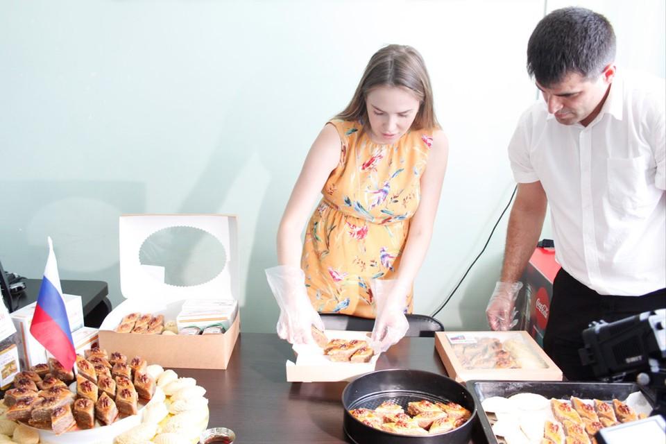 Участники акции бережно укладывают сладости в коробки.