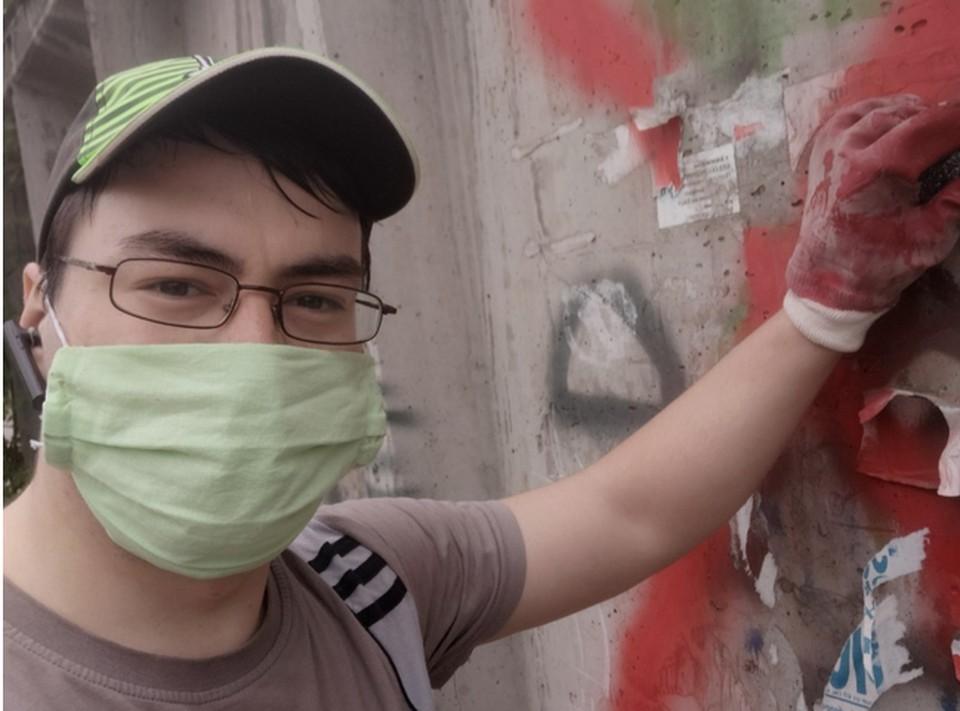Ильдар Баймуратов пытается оттереть плохое слово со стены у школы. Фото: из личного архива героя публикации.