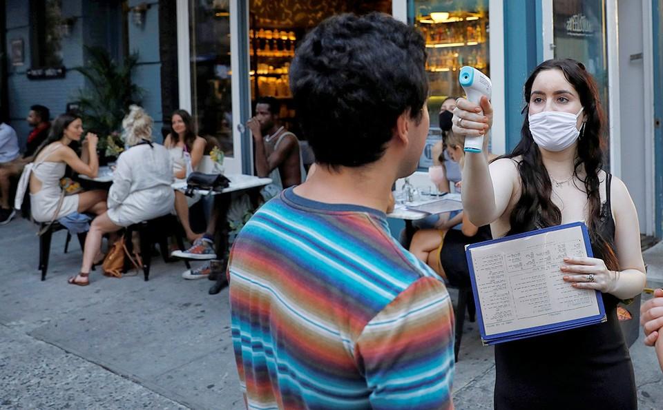 Проверка температуры у гостя ресторана в Нью-Йорке.