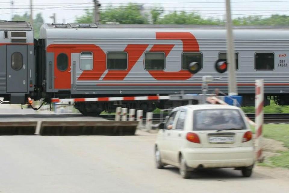 Пассажирский поезд на жд переезде Фото: СвЖД