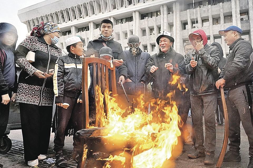Киргизы вышли на улицы Бишкека в знак несогласия с результатами парламентских выборов. Ночью 5 октября протестующие штурмом взяли здание администрации президента. Во вторник протесты продолжились, но сильно похолодало - всего +4, вот и приходится жечь костры из того, что удалось найти в разграбленном здании. Фото: EPA/ТАСС