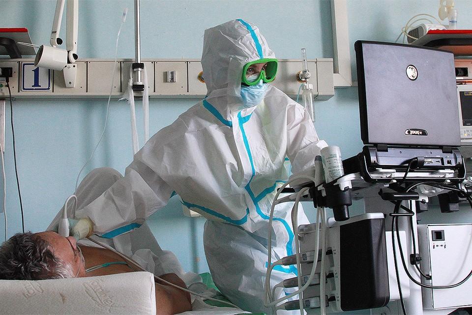 Врач обследует пациента отделения для зараженных коронавирусной инфекцией COVID-19 в больнице Иркутска.