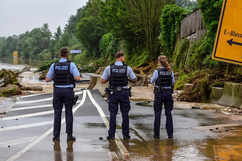 Полицейские у разрушенной водой автотрассы в городе Эрфтштадт, Германия.