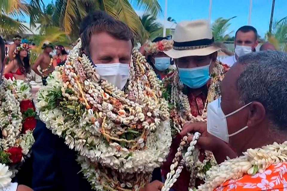Один за другим на Макрона стали вещать венки из цветов, что является символом почета и уважения во Французской Полинезии.