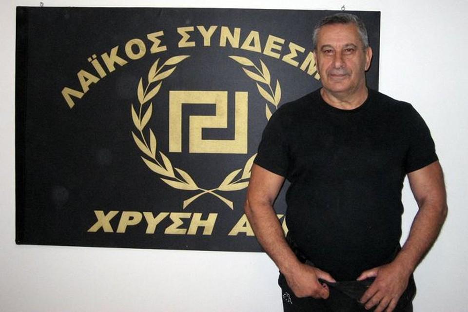 Один из лидеров афинских националистов Янис Вулдис на фоне эмблемы своей партии - древнегреческой свастики.