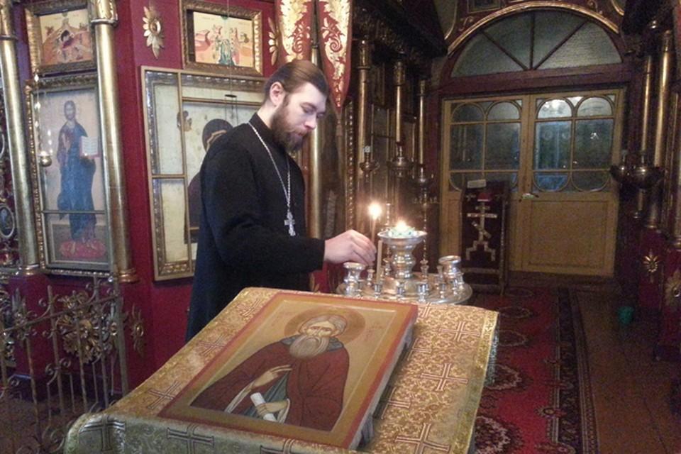 Отец Богдан ставит свечку