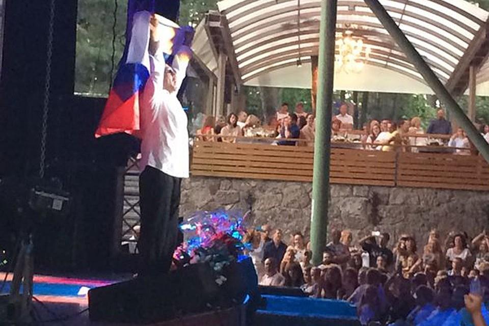 Зрители, коих был полон зал, встретили артиста овациями, когда он появился на сцене, гордо неся над собой российский флаг