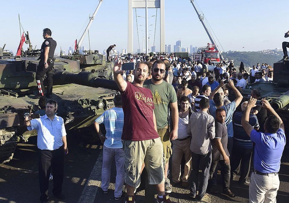 Жители Стамбула фотографируются у моста через Босфор после того, как оборонявшие его военные сложили оружие.