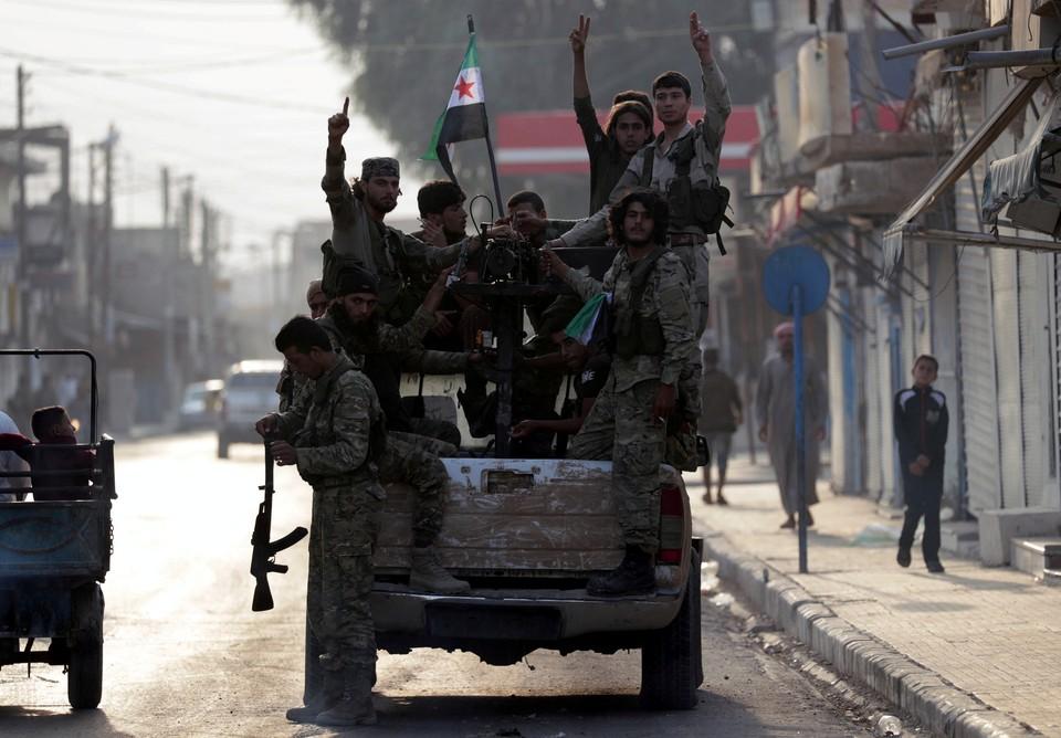 Бойцы сирийской оппозиции, поддерживаемые турецкими военными, на улицах города Таль Абад, север Сирии.
