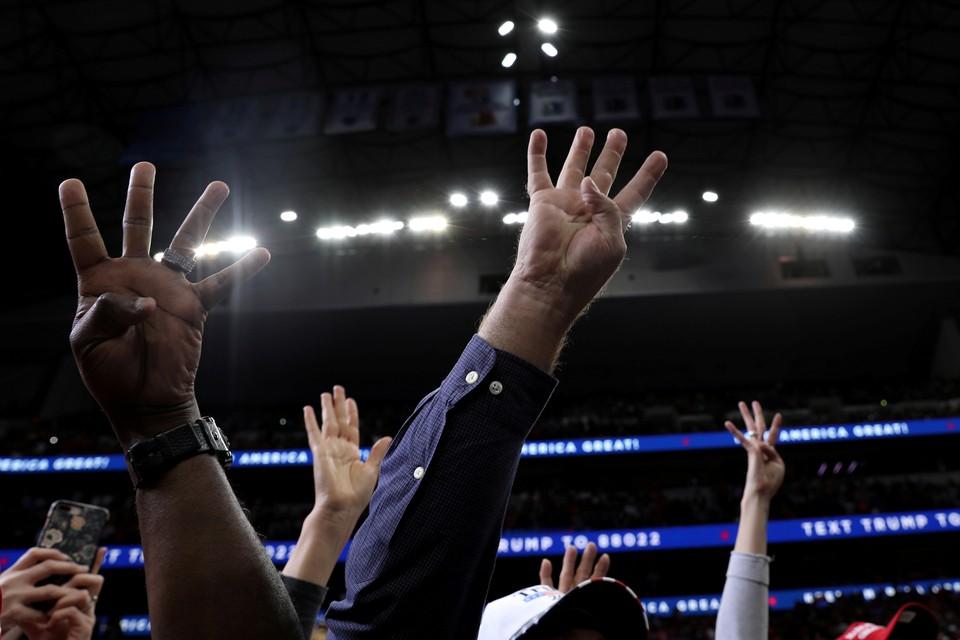 """Сторонники Дональда Трампа демонстрируют жест """"еще четыре года"""" во время предвыборного митинга в Техасе."""