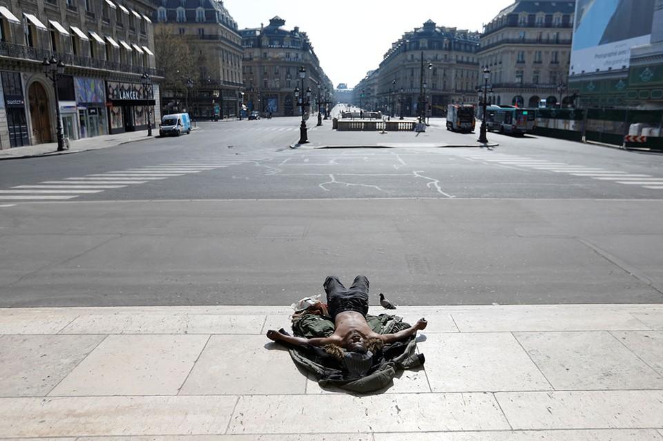 Бездомный спит на лестнице возле пустынной площади Оперы в Париже во время карантина по коронавирусу.