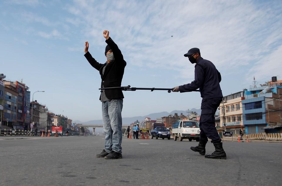 Непальский полицейский задерживает специальным устройством, позволяющим соблюдать дистанцию, человека, нарушившего карантин.