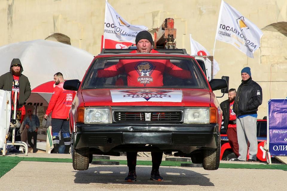 """Спортсмен несет автомобиль во время турнира """"Люди сильнее машин"""" в Севастополе"""