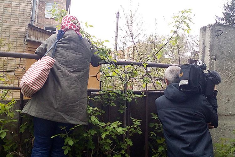 Нелегкий труд журналистов, пытающихся разглядеть хоть что-то за забором.