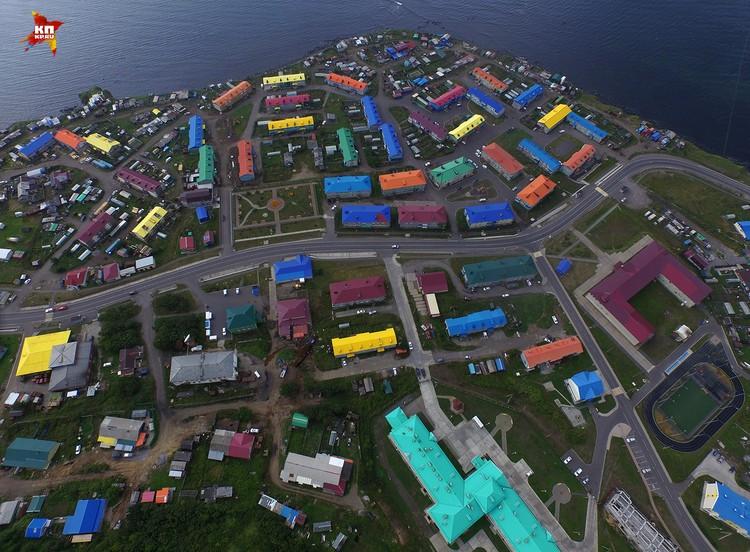 В Курильке все дома раскрашены в яркие цвета и при взгляде сверху хороно видны два крупных здания - больница и школа с футбольным полем