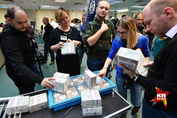 Журналисты изучают стопки с купюрами.