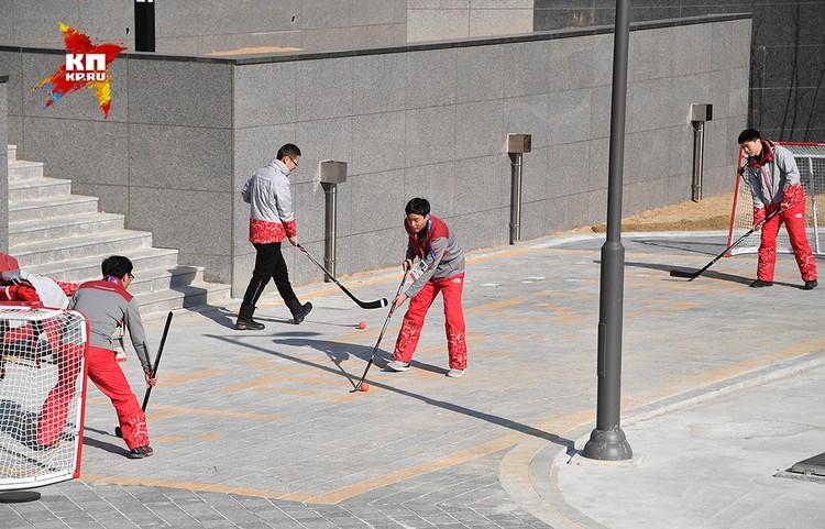Волонтеры коротают время за игрой в хоккей.