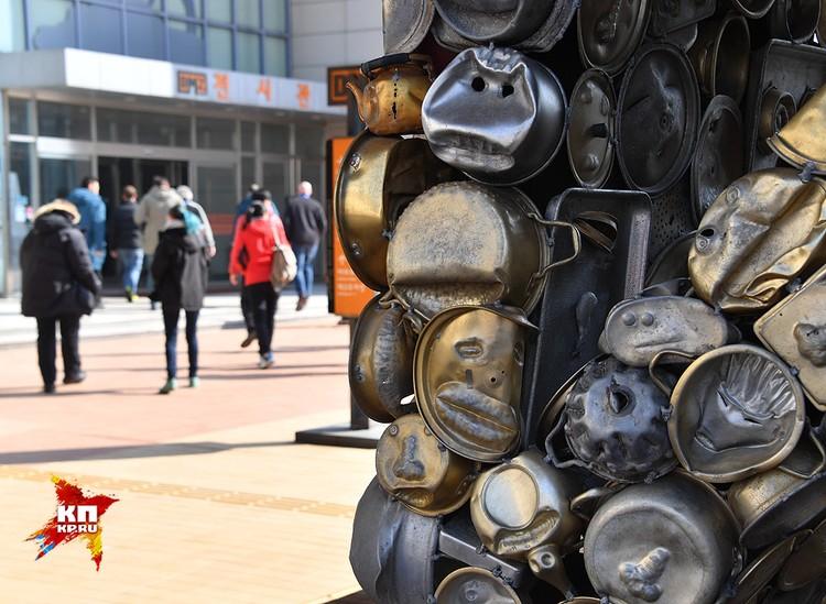 Из предметов времен войны здесь металлические миски, инсталированые под выражения лиц и гримас их владельцев.