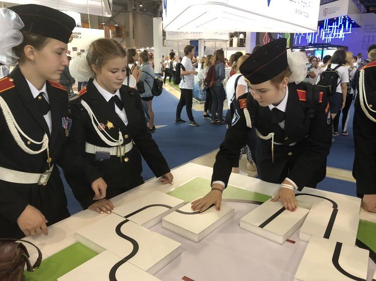 Девчушки с большими бантами и в строгой кадетской форме строят дорогу для машин-роботов