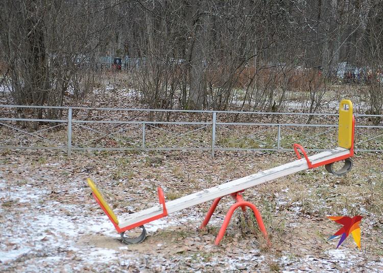 Пустующая детская площадка с видом на кладбище.