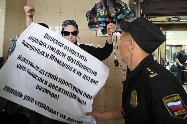 Активистка с плакатом у здания суда. Фото Сергей Бобылев / ТАСС