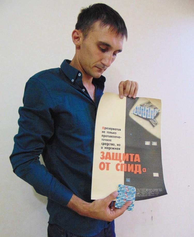 """Дмитрий собирает не только контрацепцию, но и социальную рекламу о ней. Здесь он демонстрирует советский социальный плакат с изображением презервативов, которые в народе называли """"пулеметная лента""""."""