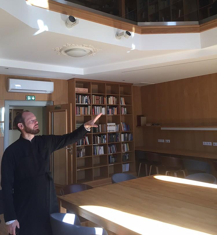 Отец Филипп показывает библиотеку.