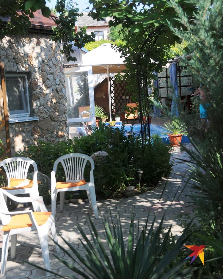 Обычный гостевой дом в Черноморском снаружи: хозяева постарались, чтобы был пусть и маленький, но бассейн и побольше цветов и зелени.