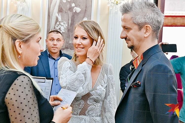 Жених не без скепсиса внимает разъяснениям работницы загса: чай, не в первый раз женится. А вот невеста заметно волнуется.