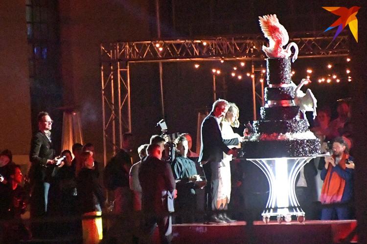 Молодожены разрезали огромный торт с шоколадным лебедем наверху.