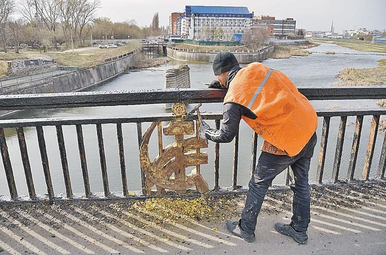 Символично: гастарбайтер счищает осыпавшуюся «позолоту» с советского серпа и молота на мосту в Туле. Чтоб позолотить заново...