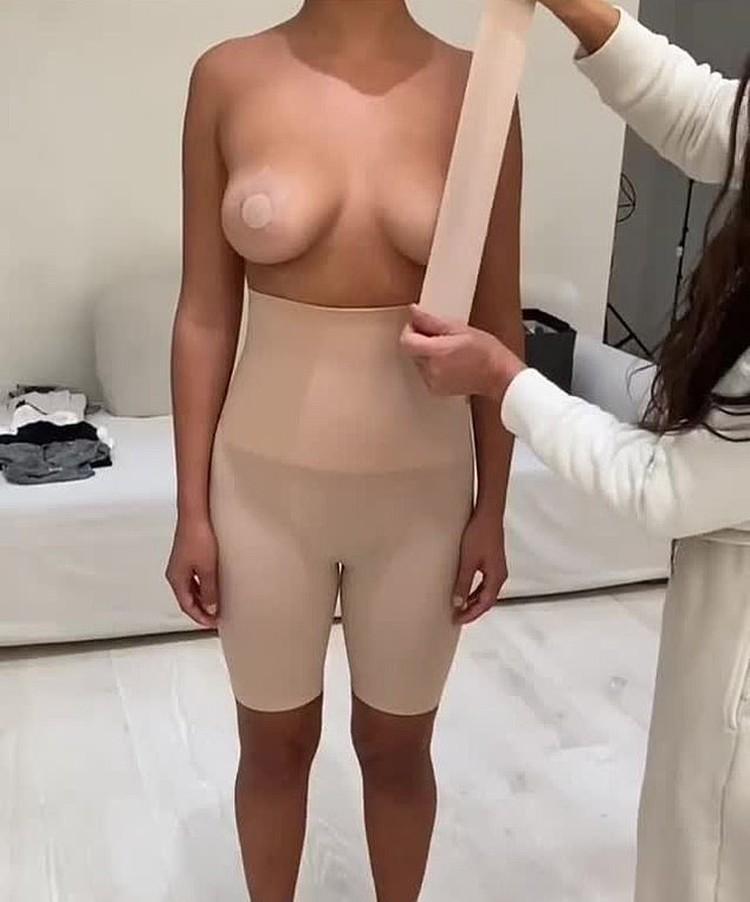 Ким опуликовала в сториз несколько роликов, в которых она собственноручно приклеивает клейкую ленту к обнаженной груди модели. Фото: Инстаграм.