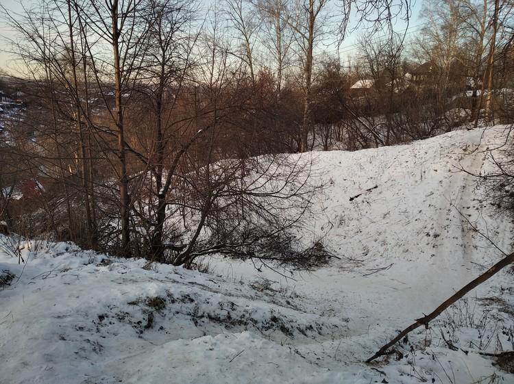 Дети в логу катаются на ледянках и снегокатах.