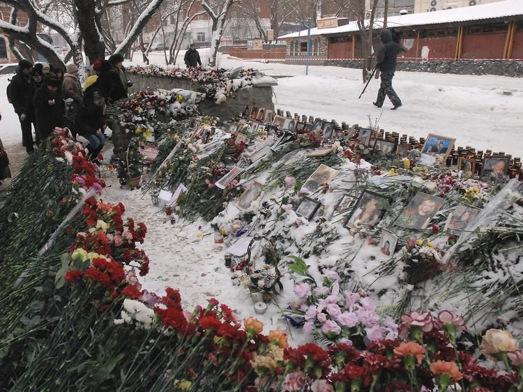 Люди несли к клубу цветы, фотографии и свечи