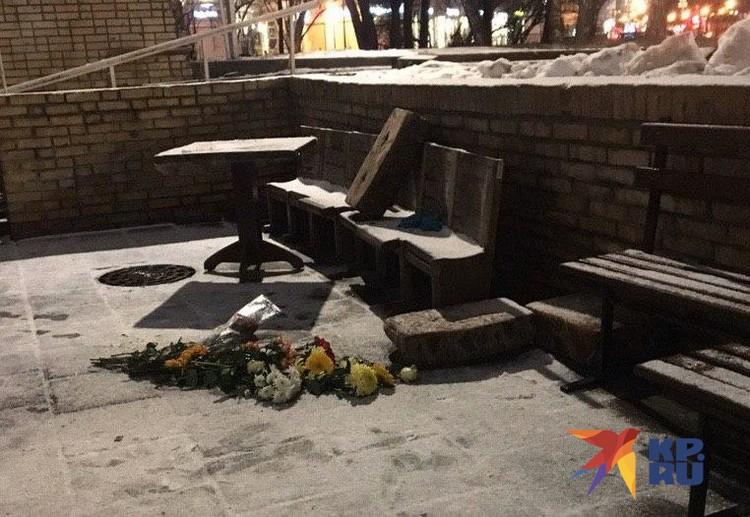 Люди с цветами подходят к храму и кладут букеты на черный незапорошенный след, в котором угадывается фигура человека.